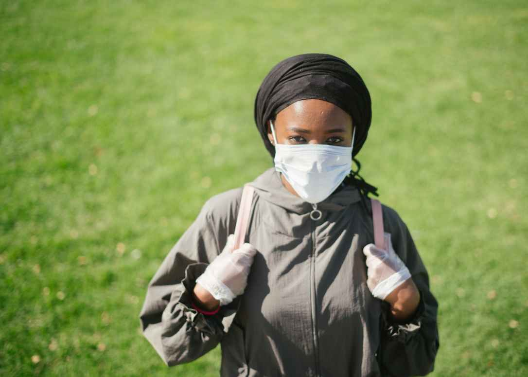 ethnic woman in protective mask and gloves on lawn