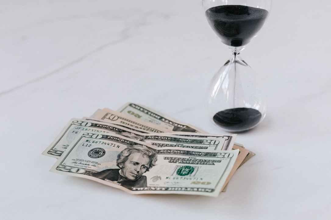 hourglass near heap of american dollars